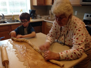 My son and Grandma roll up the dough for cinnamon rolls.