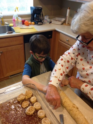 Grandma shows my son how to slice each cinnamon roll with a piece of thread.